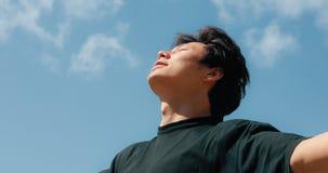 Mens het ontspannen op een vrijheid, blauwe hemelachtergrond stock footage