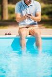 Mens het ontspannen poolside Stock Afbeeldingen