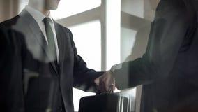 Mens het overhandigen aktentas aan de een andere mens in pak, geheime overdracht royalty-vrije stock afbeeldingen
