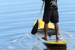 Mens het praktizeren Tribune op Peddel in de wateren van Meer Igapà ³ Royalty-vrije Stock Afbeeldingen