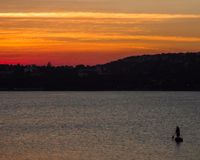 Mens het Roeien Boot bij Zonsondergang Royalty-vrije Stock Afbeeldingen