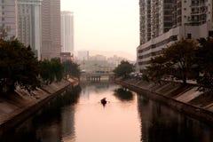 Mens het roeien boot door stad Stock Fotografie