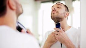 Mens het scheren baard met snoeischaar bij badkamers stock videobeelden