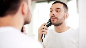Mens het scheren baard met snoeischaar bij badkamers stock video