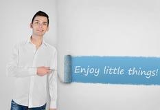 Mens het schilderen geniet van klein dingenwoord op muur Royalty-vrije Stock Foto's