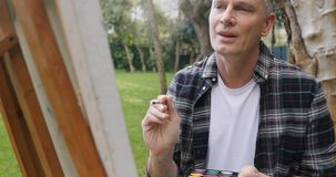 Mens het schilderen op canvas in de tuin 4k stock video