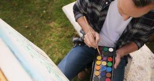 Mens het schilderen op canvas in de tuin 4k stock footage