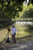 Mens het schilderen op rivieroever Stock Foto's