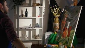Mens het schilderen stillevenbeeld op canvas in kunststudio stock videobeelden