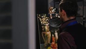 Mens het schilderen stillevenbeeld op canvas in kunststudio stock footage