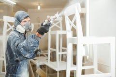 Mens het schilderen stoel in witte verf in ademhalingsmasker Toepassing van vlam - vertrager die brandbeveiliging verzekeren royalty-vrije stock foto