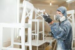 Mens het schilderen stoel in witte verf in ademhalingsmasker Toepassing van vlam - vertrager die brandbeveiliging verzekeren stock foto