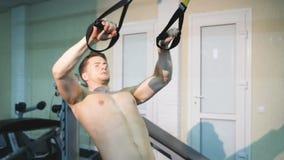 Mens het schudden dient de zaal TRX in, een mens die oefeningen op zijn handen doen stock video