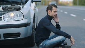 Mens het siitting dichtbij gebroken auto en het verzoeken van hulp stock footage