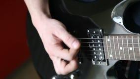 Mens het spelen bemiddelaar de elektrische gitaar stock footage