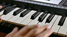 Mens het spelen de hand van de pianosynthesizer over sleutels in werking die wordt gesteld die stock video