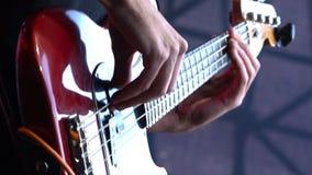 Mens het spelen gitaar bij een rotsoverleg Bass Guitar-close-up stock video