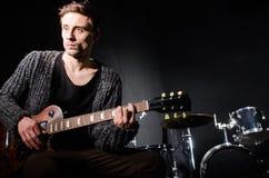 Mens het spelen gitaar in donkere ruimte Royalty-vrije Stock Afbeelding