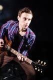 Mens het spelen gitaar in donkere ruimte Royalty-vrije Stock Afbeeldingen