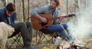 Mens het spelen gitaar en vriend het strijken hond samen rond brandplaats Echte vriendenmensen openlucht het kamperen tentvakanti stock video