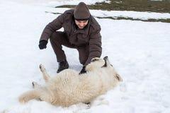 Mens het spelen met een witte hond in de winter royalty-vrije stock fotografie