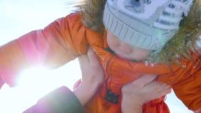 Mens het spelen met uw kind in een zonnige de wintertijd Het houden in zijn wapens Het landschap van de winter 2 video's in 1 stock video