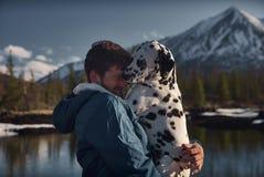 Mens het spelen met zijn terrein van de hond in openlucht berg stock fotografie