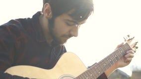 Mens het spelen op een gitaar in openlucht Speelmuziek op een akoestische gitaar stock video