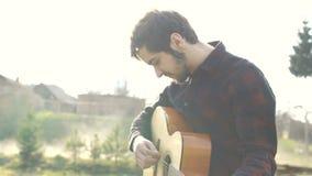 Mens het spelen op een gitaar in openlucht Speelmuziek op een akoestische gitaar stock videobeelden