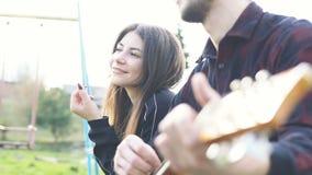 Mens het spelen op een gitaar in openlucht Speelmuziek op een akoestische gitaar stock footage