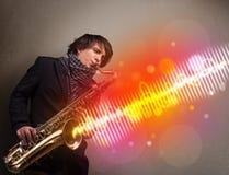 Mens het spelen op saxofoon met kleurrijke correcte golven stock foto's
