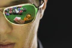 Mens het spelen pook met bezinning door zijn zonnebril stock foto