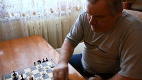 Mens het spelen schaak thuis stock videobeelden