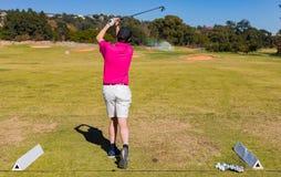 Mens het teeing weg op een golfcursus met een bestuurder stock fotografie