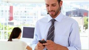 Mens het texting op telefoon terwijl de collega achter hem werkt stock video