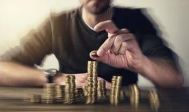 Mens het toenemen muntstukken op stapels royalty-vrije stock afbeeldingen