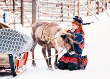 Mens in het traditionele kostuum van Saami bij Rendier in Finland in Lapland in de winter royalty-vrije stock afbeeldingen