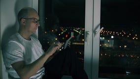 Mens het typen bericht in sociale netwerken op de zitting van PC van de het schermtablet op vensterbank stock video