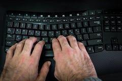 Mens het typen op een toetsenbord met brieven in Hebreeër en het Engels Stock Afbeelding