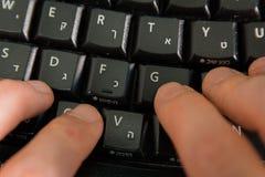 Mens het typen op een toetsenbord met brieven in Hebreeër en het Engels Royalty-vrije Stock Afbeeldingen