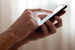 Mens het typen op een zwarte smartphone royalty-vrije stock foto