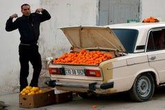 Mens het uitrekken zich in Baku, hoofdstad van Azerbeidzjan, naast auto die sinaasappelen voor verkoop in de laars tonen royalty-vrije stock foto