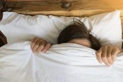 Mens het verbergen in bed onder de deken thuis stock fotografie