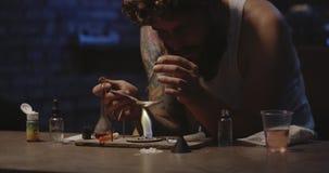 Mens het verwarmen drug in een lepel stock footage