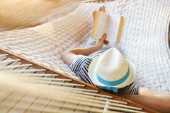 Mens in hoed in een hangmat met boek op een de zomerdag royalty-vrije stock afbeeldingen