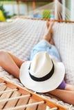 Mens in hoed in een hangmat op een de zomerdag Stock Afbeeldingen