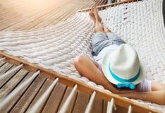 Mens in hoed in een hangmat op een de zomerdag Royalty-vrije Stock Afbeeldingen