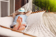 Mens in hoed in een hangmat op een de zomerdag Royalty-vrije Stock Fotografie