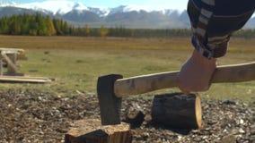 Mens in hoed met bijl die firewoods in bergen hakken Kerel met bijl stock footage