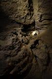 Mens in hol het ondergrondse onderzoeken Stock Foto